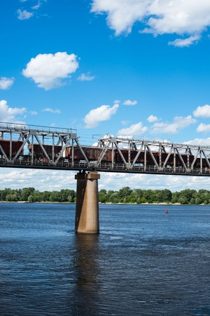 One of the piers supporting the railroad bridge across the Dnieper in Kyiv. Freight train passing across the bridge. photo