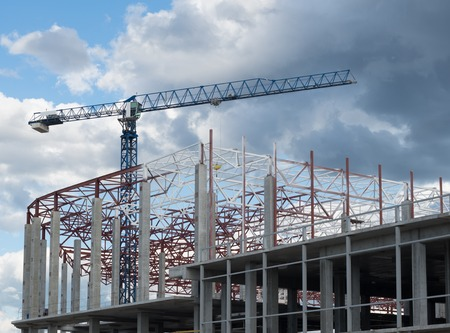 work in progress: Construction site. Framework of the new building and tower crane above it. Stock Photo