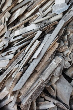 scrapheap: Pile of the old and damaged wavy roofing slates.