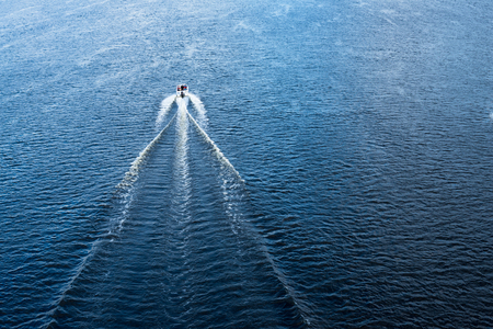 watercraft: The motor boat floating in the blue Dnieper waters.