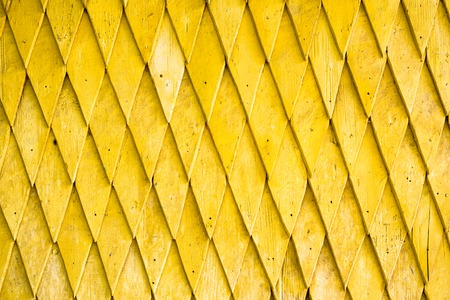 shingle: Yellow painted wooden shingle surface with rich texture.
