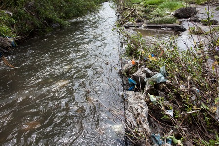 landfill site: Water pollution. Garbage near the urban stream.