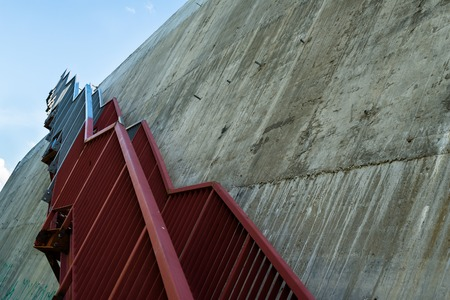 parapet wall: Metal stairs on the gray concrete wall.