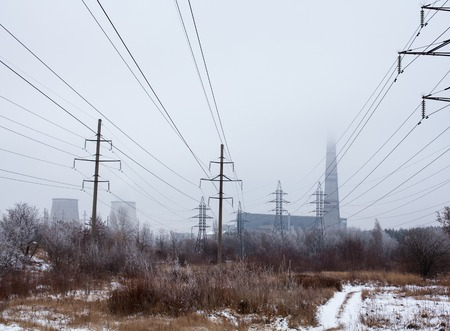 electric power station: Electricity pylons, power lines, smoke stack and cooling tower of the cogeneration plant near Kyiv (Ukraine).