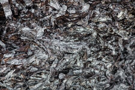 crinkly: The mass of wrinkled and charred aluminum foil.