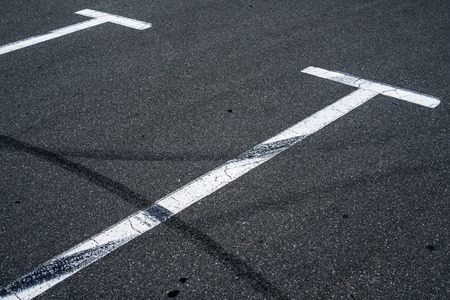 braking distance: Asphalt surface of the empty parking with white road marking lines and wheel tracks