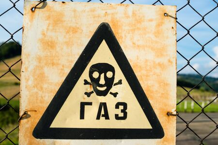 hazardous area sign: Old Gas sign (Cyrillic inscription) on the metal mesh. Close up.