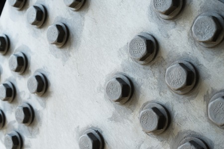 construction material: Gray metal surface with hexagonal bolt heads.