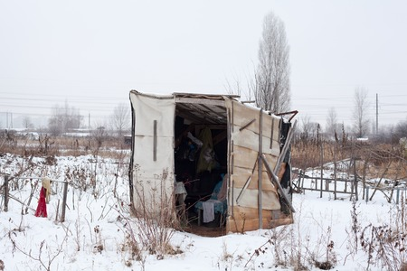 outcast: Temporary self-made shelter covered with the snow in winter.