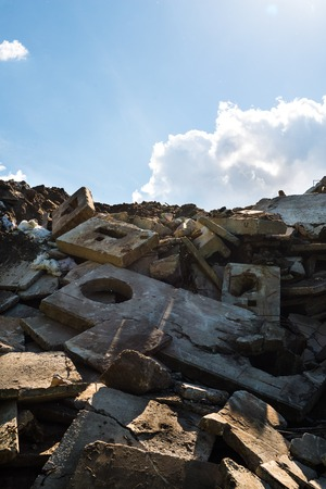spoilage: Heap of the damaged concrete blocks. Construction debris. Blue sky background,