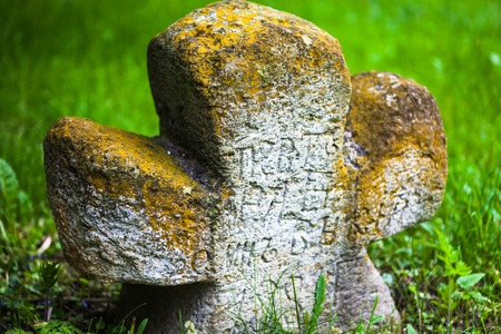 slavonic: Old moss-grown stone cross with engraved Old Church Slavonic inscriptions. Kyiv, Ukraine. Close up. Stock Photo