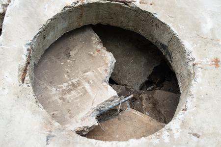 orifice: Concrete block with the manhole opening on the pile of damaged concrete blocks.