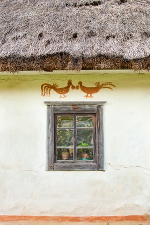 daub: Decorated window of the old traditional Ukrainian house built in wattle and daub technique with thatched roof.