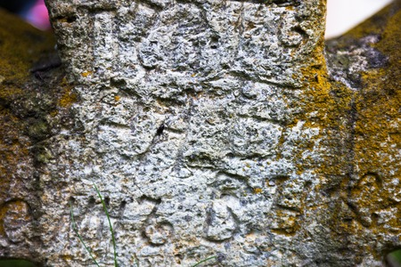 slavonic: Moss-grown surface of the old stone cross with engraved Old Church Slavonic inscriptions. Kyiv, Ukraine. Close up.