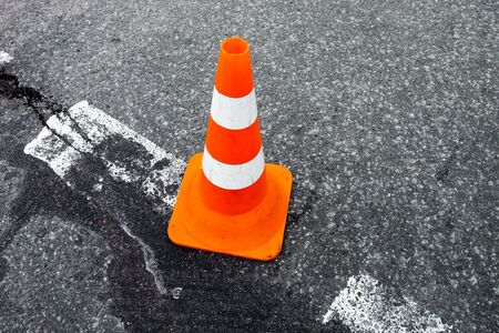 marking up: Traffic cone on the asphalt surface with partly rubbed out white road marking line. Close up. Stock Photo