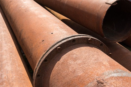 orifice: Rusty metal pipes stack on the construction site.