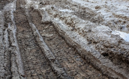 rut: Wheel tracks on the muddy dirt road after the rain. Stock Photo