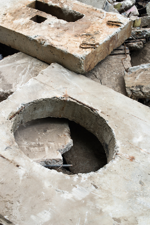 orifice: Concrete block with the manhole opening on the pile of damaged concrete blocks.