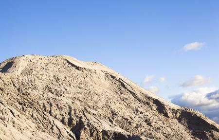 suelo arenoso: Pila de arena y el cielo azul sobre él.