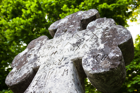 slavonic: Old cross gravestone with engraved Old Church Slavonic inscriptions. Kyiv, Ukraine. Close up. Stock Photo