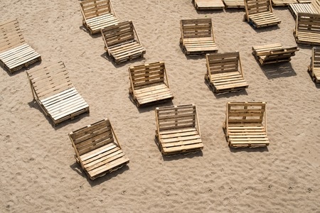 Deck chairs made of wooden cargo pallets on the empty beach.