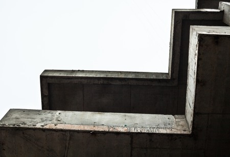 unfinished building: Concrete surfaces of the unfinished building against the white sky