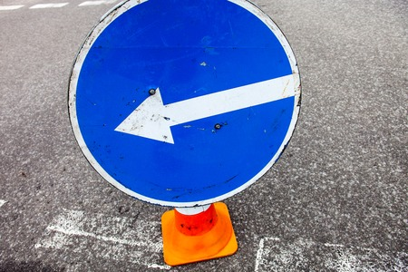 turn left sign: Turn left sign on the traffic cone. Close up. Stock Photo