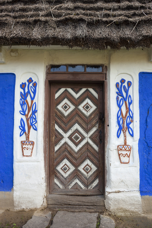 daub: Decorated door of the old traditional Ukrainian house built in wattle and daub technique with thatched roof. Stock Photo