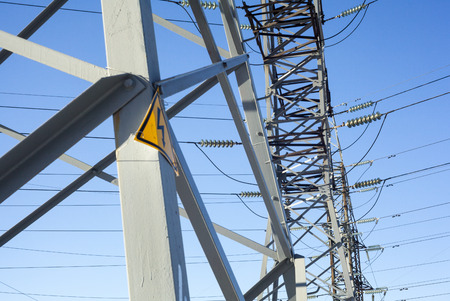 electricity grid: Electricity pylons with warning high voltage sign Stock Photo