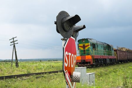 freight traffic: Traffic lights and signs at the railroad crossing and the approaching freight train (Ukraine).