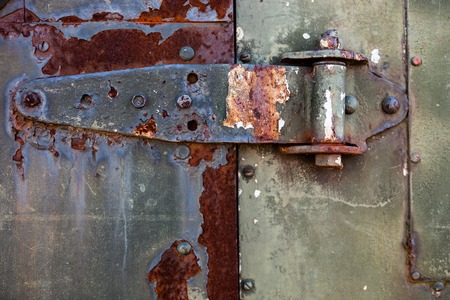 furniture hardware: Old rusty metal hinge on the rusty metal door with cracked gray paint Stock Photo