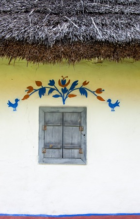 daub: Decorated window of the old traditional Ukrainian house built in wattle and daub technique with thatched roof and closed shutters.