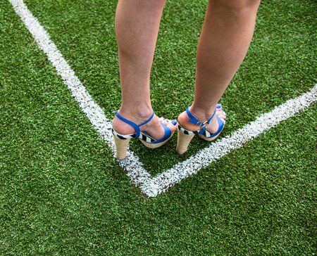 touchline: Woman legs in high heel sandals on the soccer field near the white line