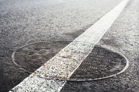 carriageway: Manhole cover on the road with white road marking line on it.