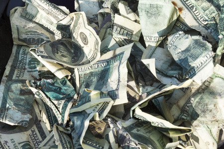dinero falso: Pile of crumpled one hundred-dollar bills on the ground.