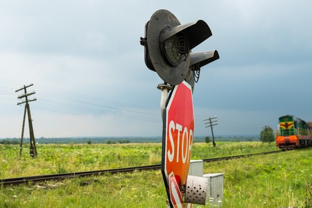 Traffic lights and signs at the railroad crossing and the approaching train (Ukraine). Standard-Bild