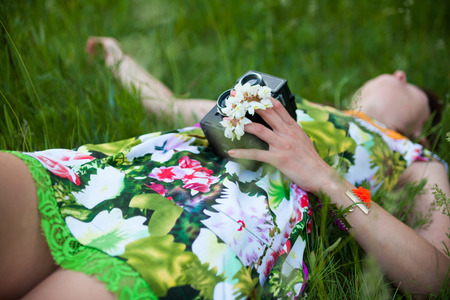 Sexy woman with vintage camera lying in the grass.