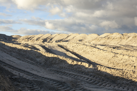 sand quarry: Piles of sand with caterpillar traces against the cloudy sky.