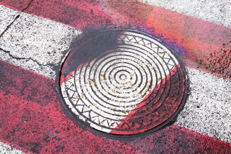 Manhole on the white and red zebra crossing after the rain.