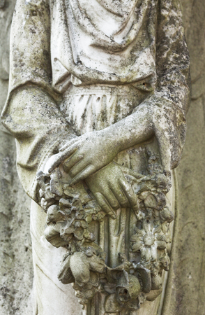 Womans hands holding the wreath. Old cemetery marble sculpture detail. Standard-Bild
