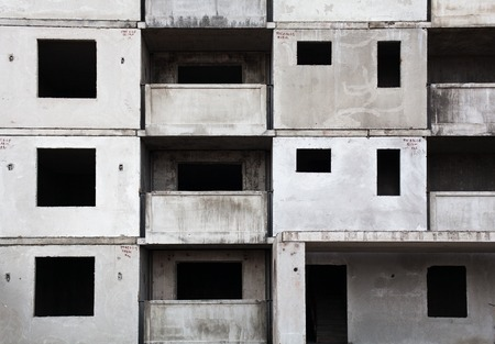 Unfinished grey concrete building in the construction site. Standard-Bild
