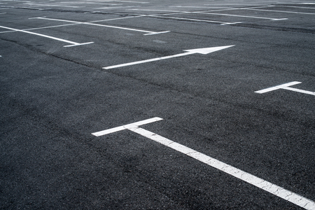 Asphalt surface of the empty parking with white road marking lines