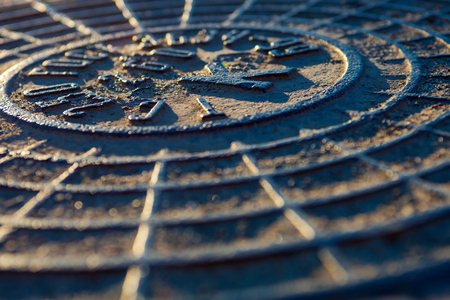 Close-up of the metal manhole cover in the sunshine.