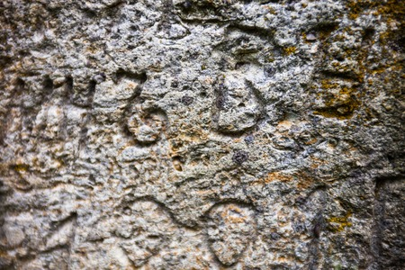 Moss-grown surface of the old stone cross with engraved Old Church Slavonic inscriptions. Kyiv, Ukraine. Close up.