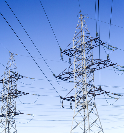 System of the electricity pylons against the blue sky. Banque d'images