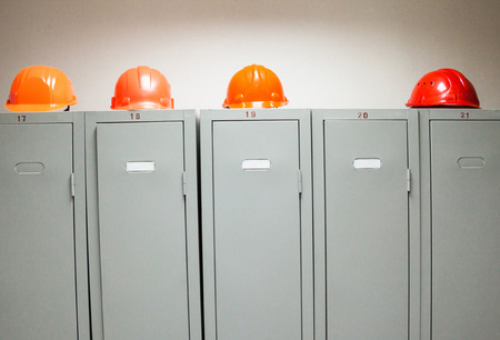 Metal lockers and plastic hard hats in the cloakroom of the industrial plant. Banque d'images - 109558564