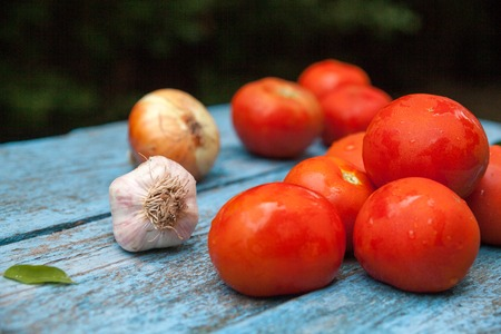 Wet red tomatoes, onion and garlic on the wooden table. Fresh ripe summer vegetables. Vegetarian food. Preparing the salad. Close-up.
