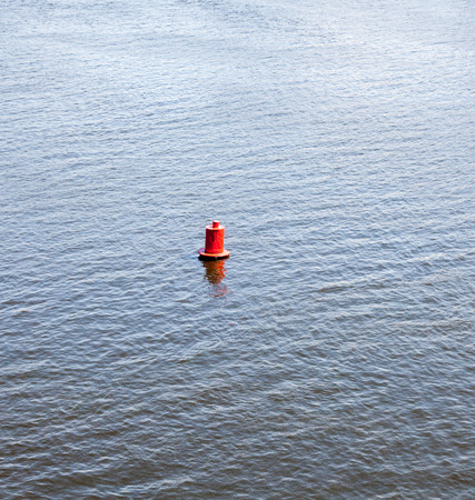 Red round buoy on the water surface.