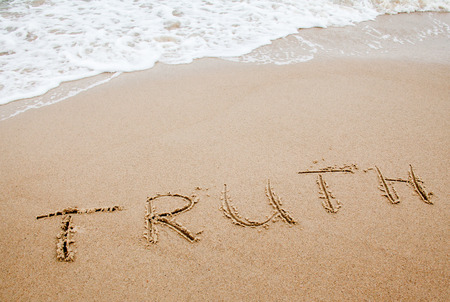 Word truth written on the sand near the sea. Sea waves rolling onto the beach. Stok Fotoğraf