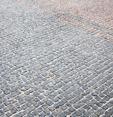 Road paved with gray and pink setts. Road pavement.